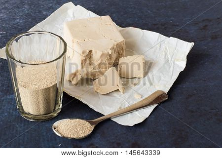 The dry granular yeast in a glass and in spoon, fresh yeast on paper on a blue background.
