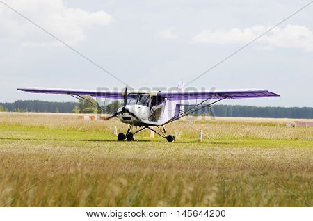 Private propeller-driven airplane standing on green grass