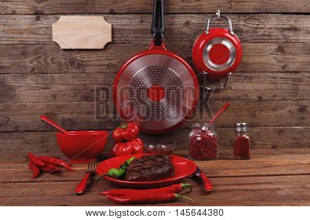 red theme lunch : fresh grilled bbq roast beef steak red plate green chili tomato soup ketchup sauce paprika small glass ground pepper american modern cutlery served wood table with empty nameplate