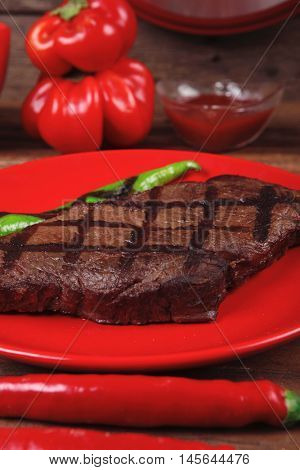 red theme lunch : fresh grilled bbq roast beef steak red plate green chili tomato soup ketchup sauce paprika small jug glass ground pepper american peppercorn and modern cutlery served on wooden table