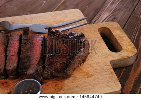 fresh roast red beef meat fillet mignon cutted on wooden plate with vintage fork many different kinds of dry spice over table