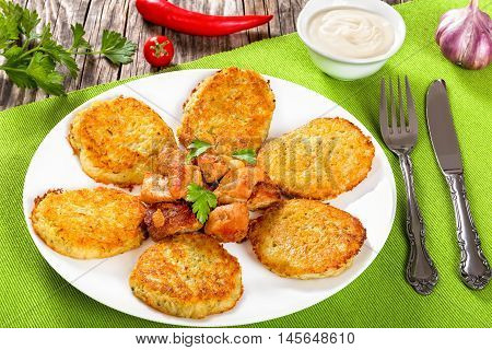 Crispiest Shredded Hash Browns with fried meat and onion on white plate on table mat view from above close-up