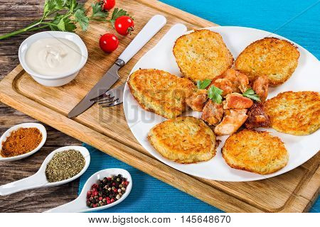 Crispiest Shredded Hash Browns with fried meat and onion on white plate on cutting board on table mat spices in porcelain spoons on wooden table view from above close-up