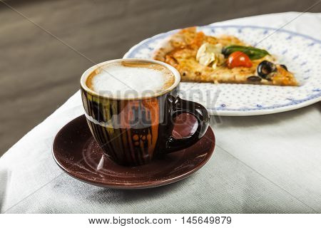 Cup with chocolate and spoom and pizza slice