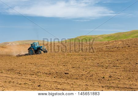 agricultural work in processing cultivation of land in Kazakhstan. Ploughing heavy tractor during cultivation agriculture works at field with plough