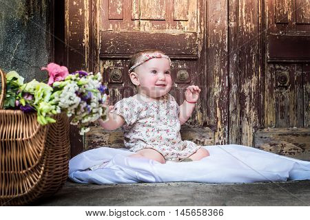 Portrait of beautiful smiling baby girl on the background of the vintage old door. Close-up