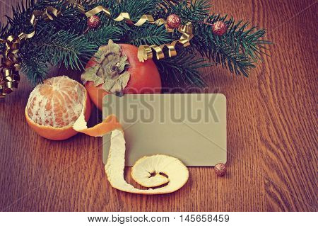 Christmas background with ripe persimmons and tangerine on wooden table paper blank