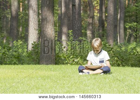 Smart boy using a tablet outdoors. Casual clothes. Technology, education, lifestyle, people concept
