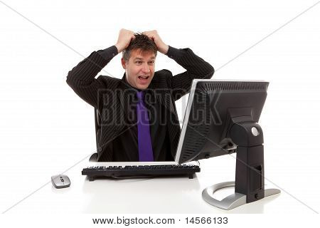 Businessman Sitting Behind Desk Is In Despair, Pulling His Hair