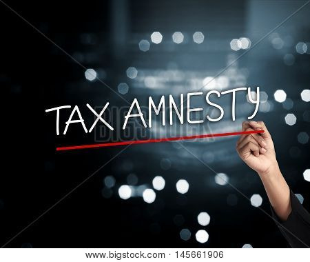 Hand Holding Pen And Write Tax Amnesty Words, Sparks Light Background