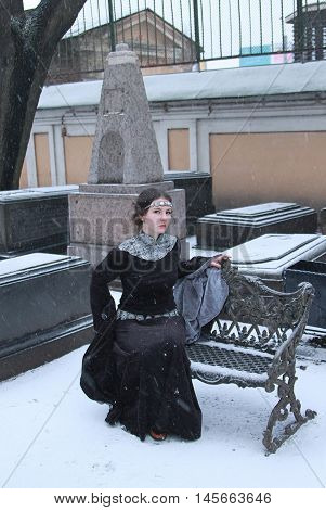 Photo of woman in long black dress with long sleeves in winter time. Fairy tale or historical picture. Helloween story.