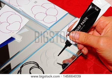 LICHFIELD, UNITED KINGDOM - OCTOBER 18, 2015 - Using relief paste to stencil flower outlines onto a mirror ready for glass painting England UK Western Europe, October 18, 2015.