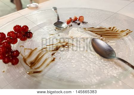 plate with sweet food residues and two teaspoons and currant