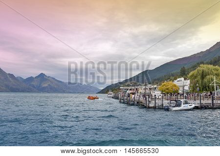 Queenstown New Zealand - March 2016: Boat piers at Queenstown lakefront by Lake Wakatipu New Zealand with speed jet boat seen in distant