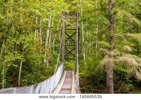 Photo of wooden suspention bridge in countryside.