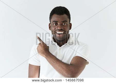 Headshot Of Handsome Young African Man In White Polo Shirt Looking And Smiling At Camera With Cheerf