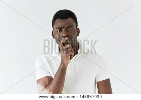 Dark-skinned Male With Mistrustful Look Posing Against White Concrete Wall. Good-looking African Man