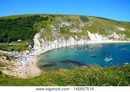 LULWORTH COVE, UNITED KINGDOM - JULY 19, 2016 - View looking down the hillside towards the cove with tourists enjoying the beach Lulworth Cove Dorset England UK Western Europe, July 19, 2016.