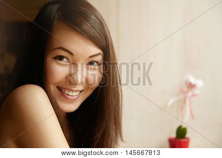 Close Up Shot Of Young Female With Brunette Hair And Healthy Skin Looking At Camera With Happy Expre