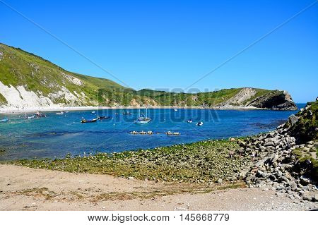 LULWORTH COVE, UNITED KINGDOM - JULY 19, 2016 - View of the beach and cove with boats moored offshore Lulworth Cove Dorset England UK Western Europe, July 19, 2016.