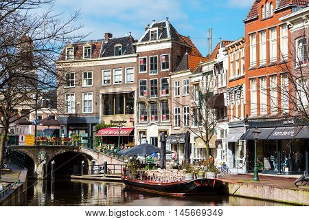 Leiden, Netherlands - April 7, 2016: Traditional houses, boat cafe  and people in downtown of Leiden, Holland, Netherlands