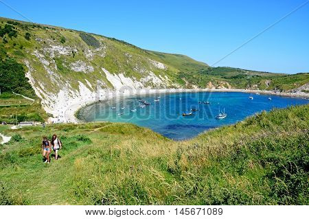 LULWORTH COVE, UNITED KINGDOM - JULY 19, 2016 - Elevated view of boats moored in the cove with tourists walking in the foreground Lulworth Cove Dorset England UK Western Europe, July 19, 2016.