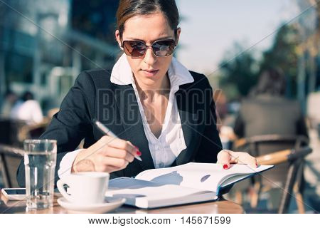 Businesswoman working in sidewalk cafe, toned image
