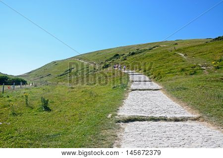 LULWORTH COVE, UNITED KINGDOM - JULY 19, 2016 - Tourists walking along a steep stepped pathway up the hillside Lulworth Cove Dorset England UK Western Europe, July 19, 2016.