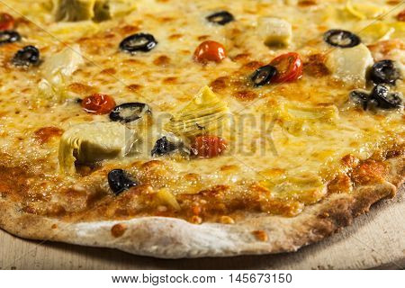 Pizza with artichokes black olives and cherry tomatoes