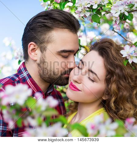 Love And Tenderness - Close Up Portrait Of Beautiful Couple Kissing In Blooming Garden