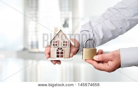 Hands with house and padlock security concept