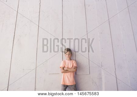 The boy stands against the wall idly . The top lot of space for text . Design resource and children's fashion .