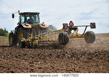 Tractor with cultivator tilled fields after harvest