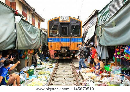 SAMUT SONGKHRAM THAILAND - SEPTEMBER 4 2016 : Mae Klong Market placed all product on railroad all vendors have to move product away when the train passes market.