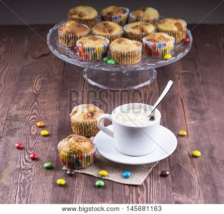 coffee with a muffin. Coffee and muffin on wooden desk