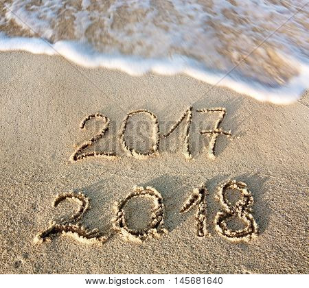 2017 2018 inscription written in the wet beach sand with sea water wave. Inscription 2017 and 2018 on a beach sand, the wave is almost covering the digits 2017.