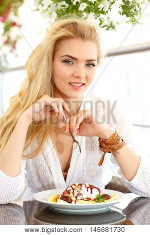 Portrait of beautiful white-headed girl, sitting in a cafe with a kind on a city