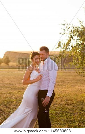 Wedding couple with glasses of champagne outdoor shot
