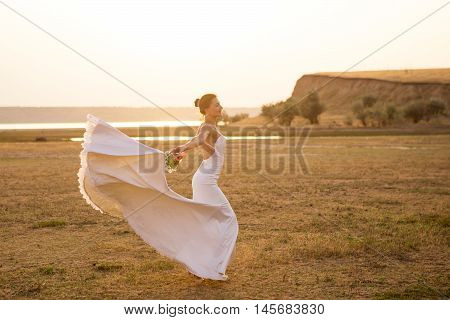 Happy bride with bouquet dancing in sunset light