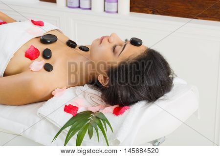 Black marble stone hot massage in spa. Female patient in wellness center. Relaxation procedure to beautiful indian girl in beauty parlor, woman lays on bed with rose petals
