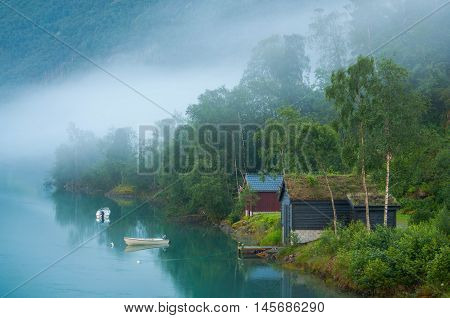 Sunrize on a foggy lake in Norway. Old houses and boats