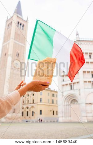 Holding a piece of Parmesan cheese on the Parma main square with italian flag on the background in Italy. Parmesan is produced mostly in the province of Parma and was named after that producing region