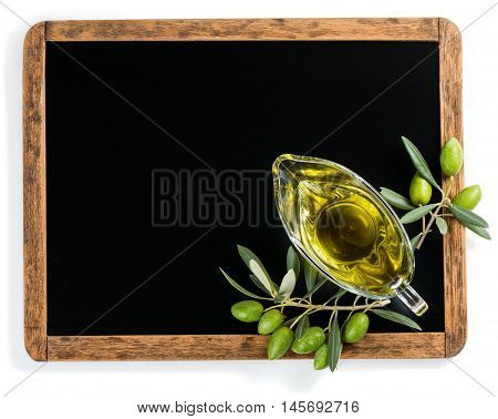 Top view of blank blackboard with olive oil in a glass sauceboat and green olive fruits over white background. Empty chalkboard for your text.