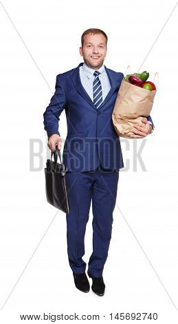 Smiling young businessman hold shopping paper bag full of groceries, vegetables and fruits, and suitcase, isolated at white background. Healthy food shopping. Full length portrait of happy man buyer