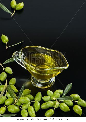 Olive oil in a glass sauceboat and green olive fruits with green leaves over black background.