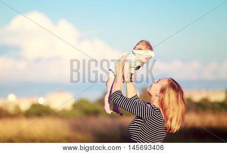 young woman playing with baby daughter outdoors. beautiful young mother tossing up a small daughter. view profile. the concept of happy family and happy parenthood. empty space for your text