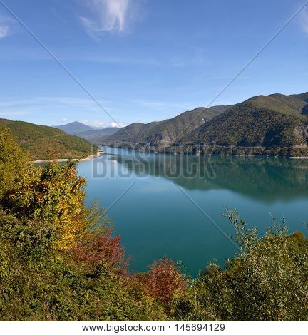 Azure lake Ananuri surrounded with autumn trees. Mountains and sky reflect in calm glassy water.