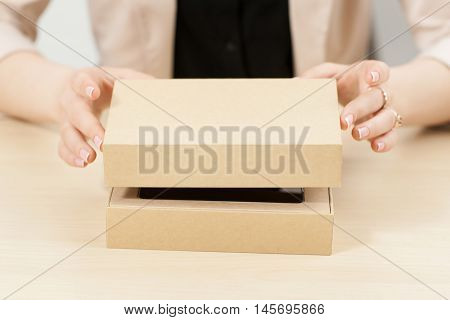 Woman opening box with new parcel, close-up. Female hands lifting lid of yellow carton package. Delivery service. online shopping, gift concept