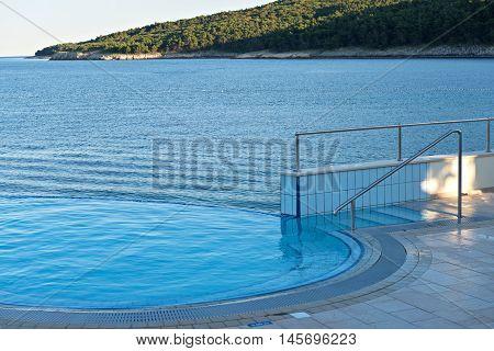 Empty infinity pool and quiet bue sea