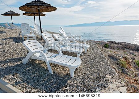 Pebble beach, chaise-longues and umbrellas in Istria, Croatian coast